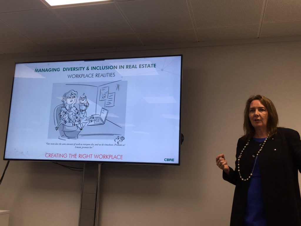 Image of Amanda Clack presenting. In the background a slide shows a female with babies trying to work on a laptop
